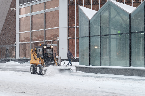 Moscow. Russia. February 12, 2021. A small loader excavator clears snow from the road along the glass walls of a modern building during a heavy snowfall. Snowflakes are flying in the air.
