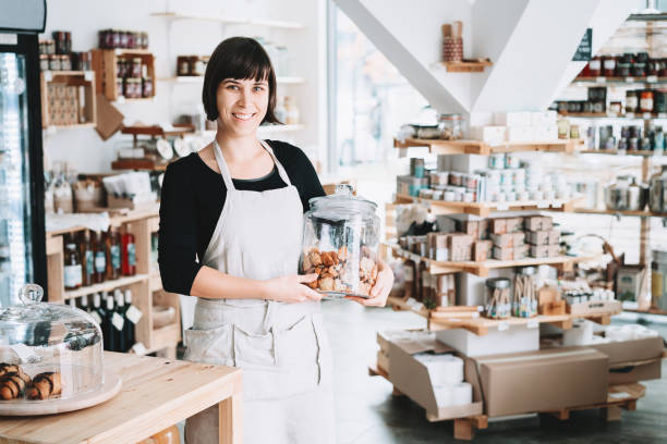 Small local business owner. Seller assistant with glass jar of pastries in interior of zero waste shop. stock photo