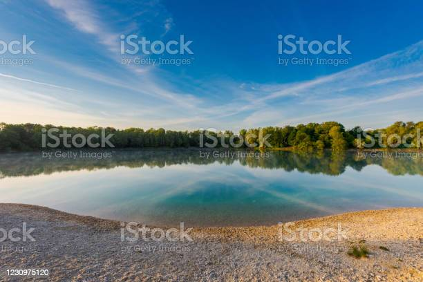 Photo of Small local recreation swimming lake in Bavaria, Germany in early morning light with fog over water