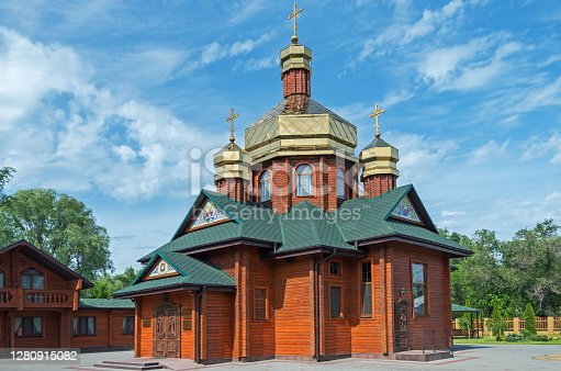 Small of log church with three gilded domes on bright sunny day