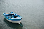 A small lonely fishing boat on calm water.
