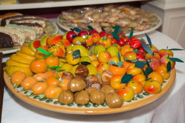 kleinen marzipan süßigkeiten in form von obst auf einer runden platte angeordnet - apfel marzipan kuchen stock-fotos und bilder