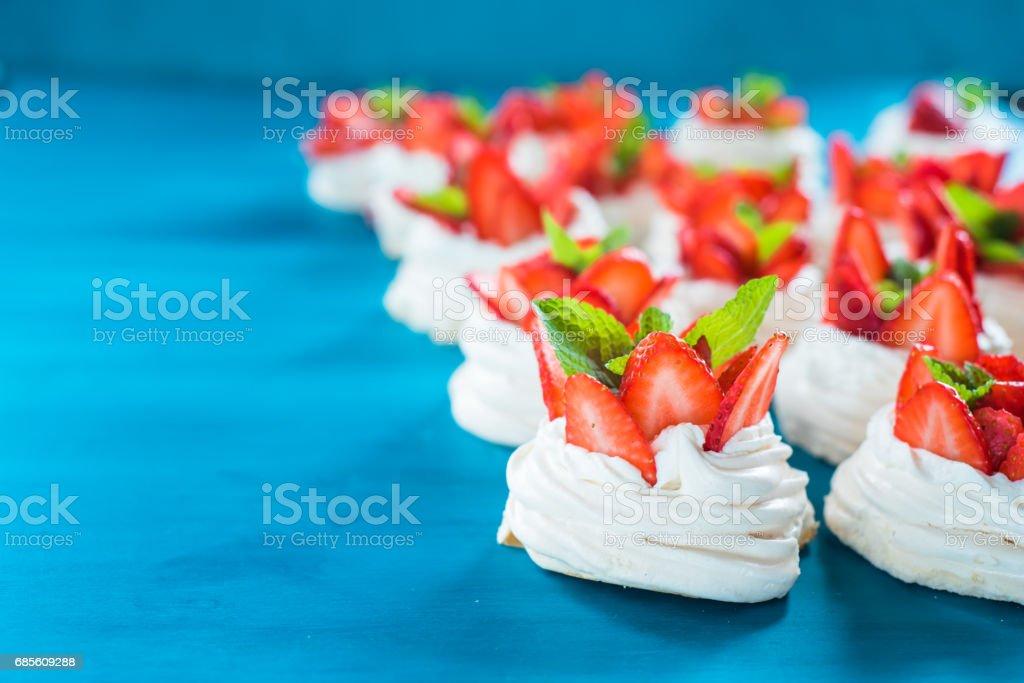 파란색 배경에 작은 랭 민트 딸기 조각 일부와 파블로 바 디저트 나뭇잎 royalty-free 스톡 사진