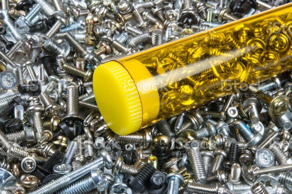 Small metal screws in the yellow box stock photo