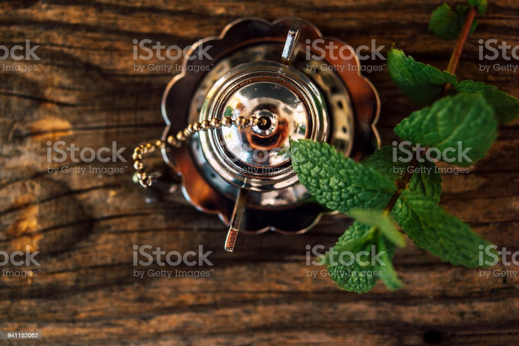 Small metal teapot with mint leafs stock photo