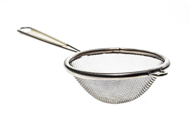 small metallic tea strainer sieve with handle isolated on white. - puderzuckersieb stock-fotos und bilder
