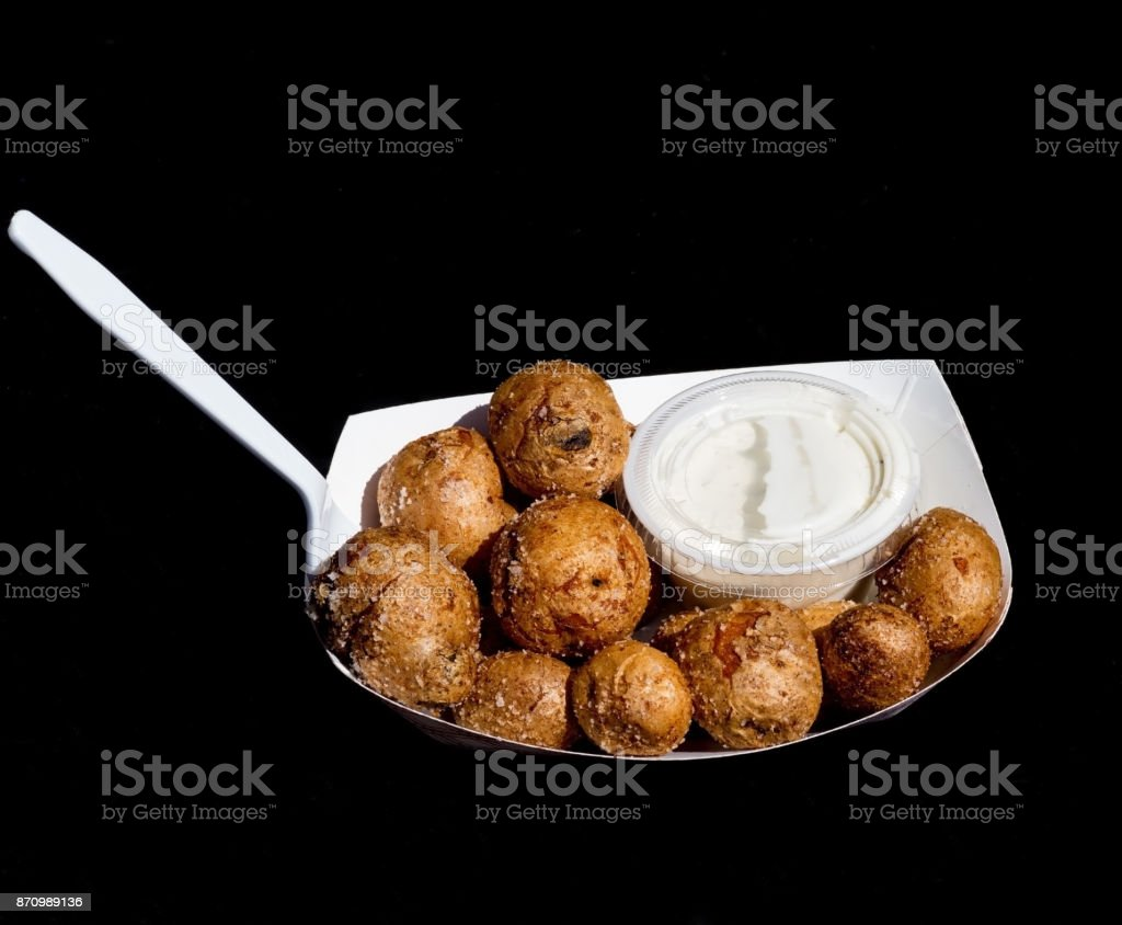 Small miniature baked potatoes sprinkled with kosher salt and a side of ranch dressing in a disposable paper tray on a black background. stock photo