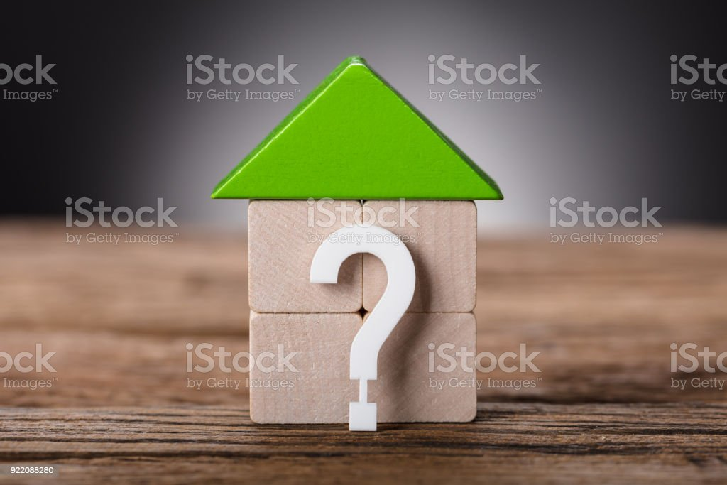 Small Model House By Question Mark On Wood stock photo
