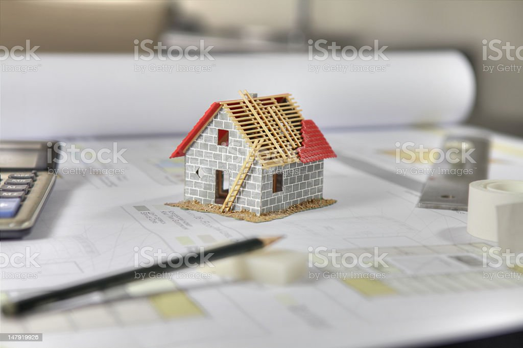 Small model of a grey brick house on an engineer's desk stock photo