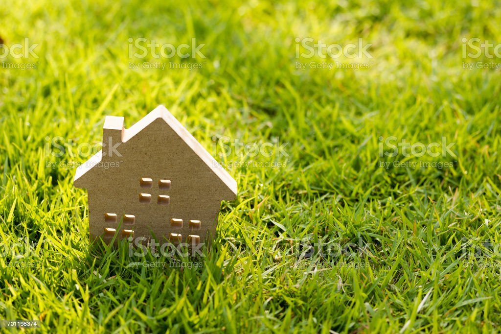 Small model of house over green grass dueling sunlight. - foto stock