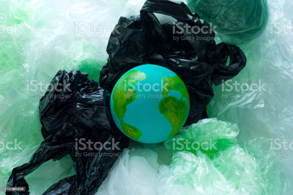 top view of a small model of the Earth planet among plastic bags,...