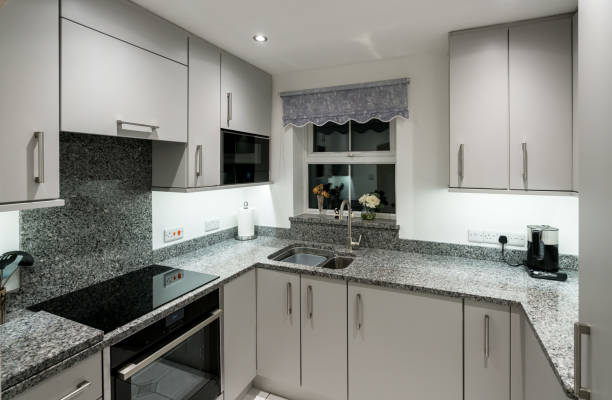 Small modern kitchen in apartment with granite worktop stock photo