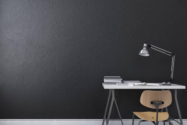 kleine moderne schreibtisch oder schreibtisch mit lampe, brille, buch und lehrstuhl an der schwarzen wand hintergrund. 3d-rendering - graues büro stock-fotos und bilder