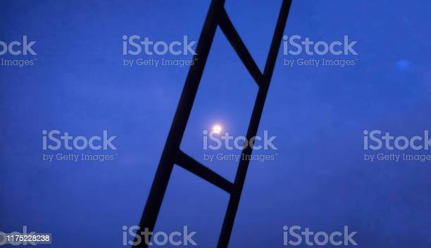 Photo of Small moon in an evening sky. beautiful photo of the moon between the ladders. moon in the blue sky.