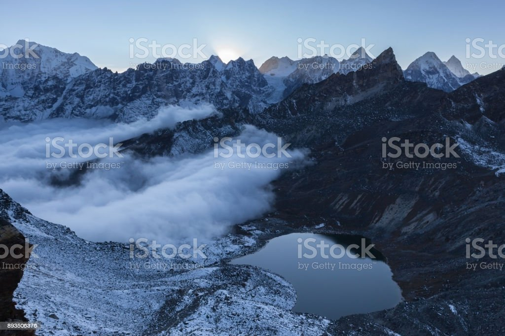 Small moraine lake and snowy mountain peaks in the early morning lights in Himalayas, Nepal. stock photo