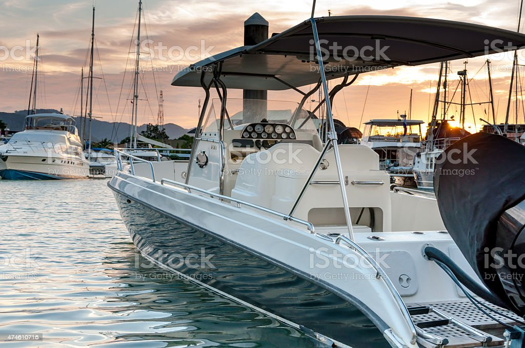 Small motorboat docking at the marina at sunset time圖像檔
