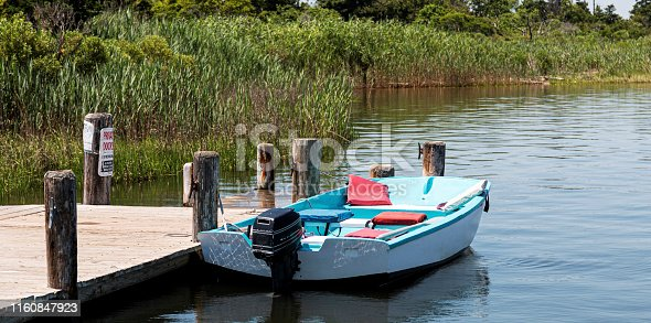 A small single engine ligh blue motorboat is tied to a wood dock in a secluded area surrounded by tall beach grass.
