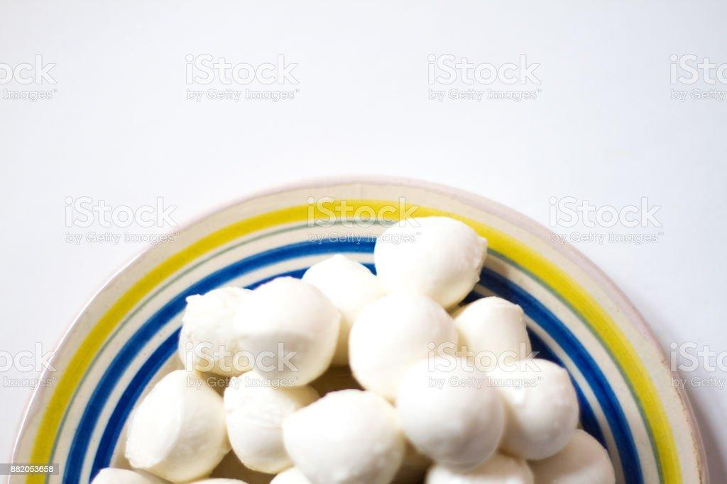 Small Mozzarella Balls (Bocconcini) on Plate, White Background stock photo