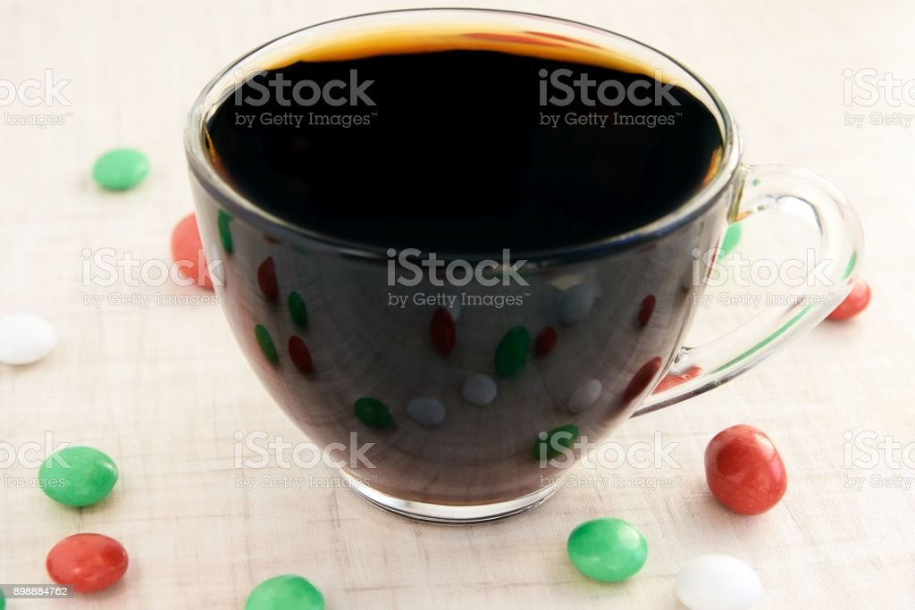 Small multi colored sweets. Hot black tea. Reflection stock photo