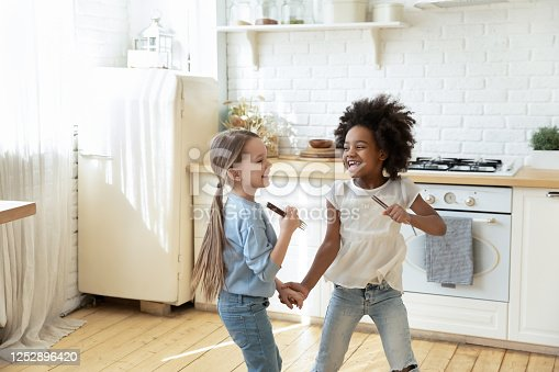 Small adorable multi ethnic girls holding hands play in kitchen holding forks dancing enjoy weekend free time in company of best friend or sister. Children having fun, playtime before cooking at home