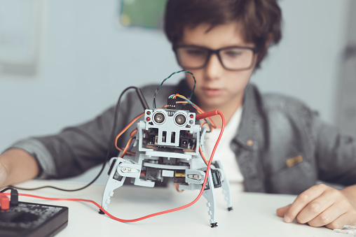 A small nerd in glasses is holding a robot. A boy in a gray shirt and glasses is sitting at a table in front of him whose robot the boy made. He is very satisfied with his work