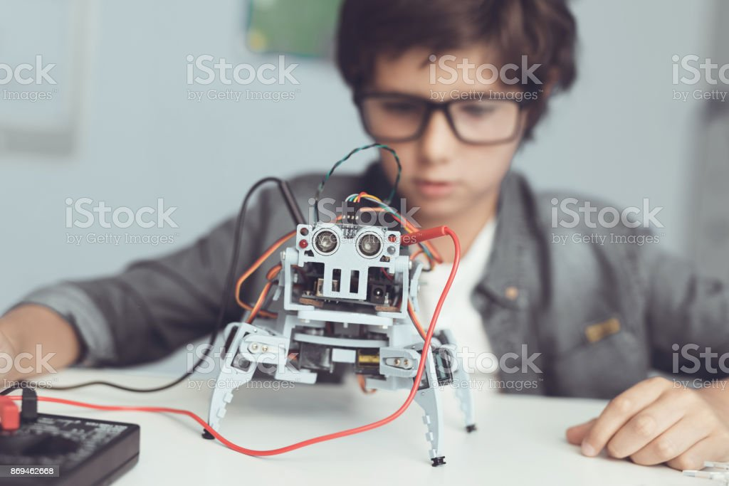 A small nerd in glasses is holding a robot. He looks carefully at his creation stock photo