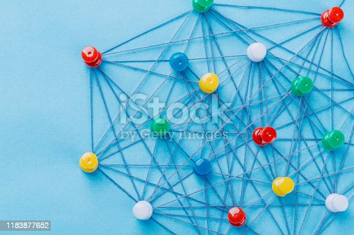 Small network of pins (Thumbtack)and string, An arrangement of colorful pins linked together with string on a pale blue background suggesting a network of connections.