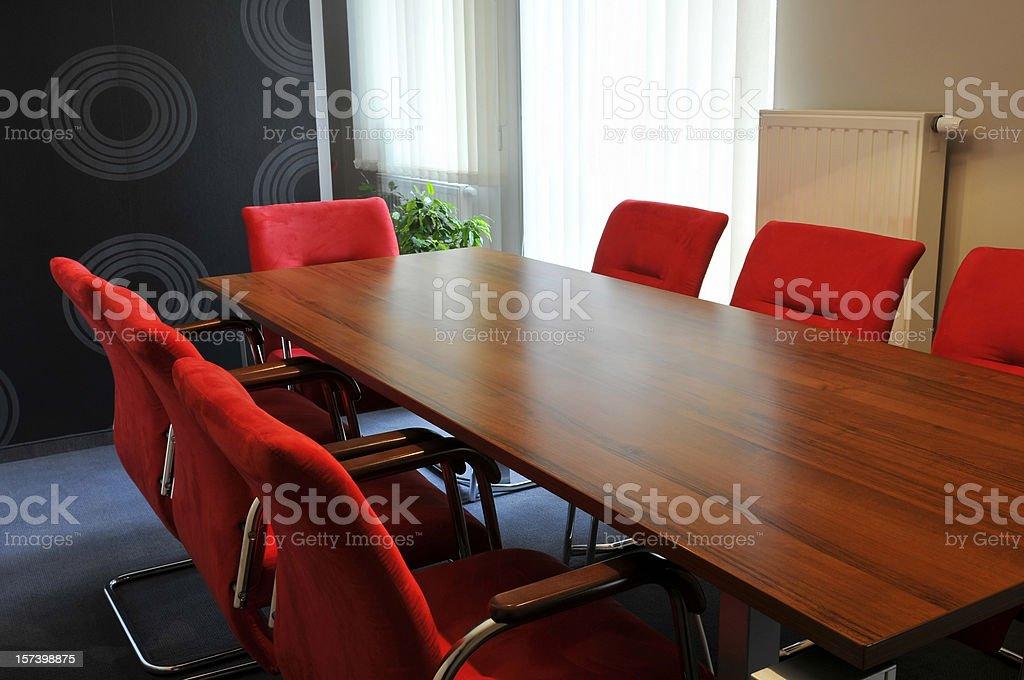 Un petit bureau avec bureau en bois rouge fauteuils confortables la