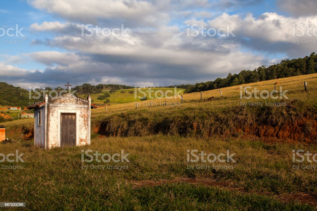 Small old white church in the countryside in a blue sky day stock photo