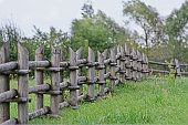 istock Small old wooden fence on open rustic field 998443858