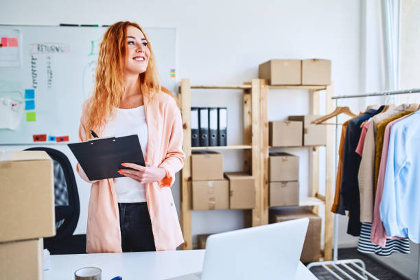Small online clothing store owner proudly standing in office space and looking away stock photo