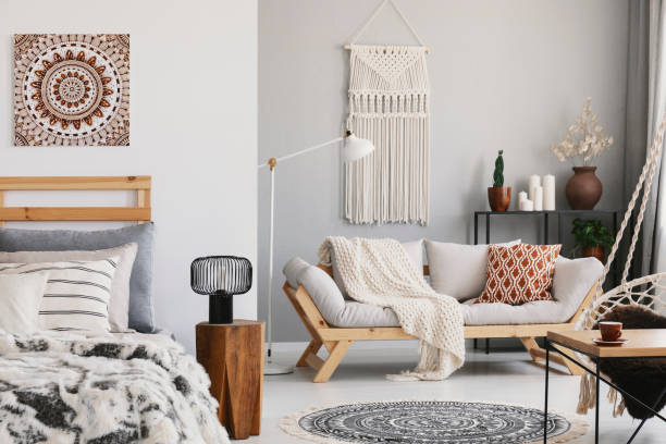 small open space flat interior with beige sofa with cushion, macrame on the wall, rack with candles and plants and bed with pillows - hygge imagens e fotografias de stock