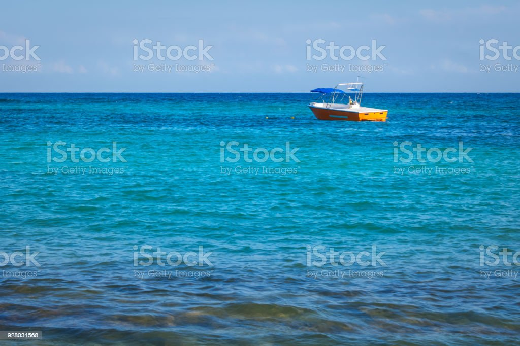Small orange fishing boat, tourist boat in open water. Tropical...