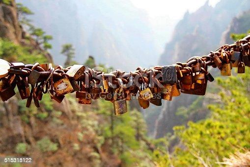 Small rusty padlocks hanging in row, Huangshan (Yellow) mountain, China