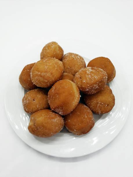 kleine pfannkuchen mit zucker auf weißem hintergrund - löcherkuchen stock-fotos und bilder