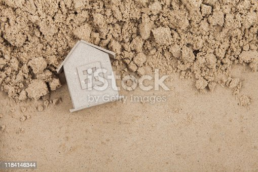 A small paper house lies on the sand from the construction site