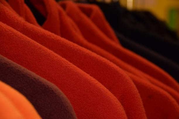 kleinen teil des bunten fleece-jacken auf kleiderbügel - fleecepullover stock-fotos und bilder
