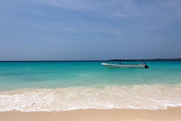 Small Passenger Boat Anchored at a Caribbean Beach stock photo