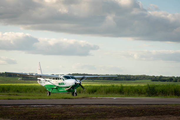 Small passenger Maya Island Air aircraft landing in  remote Orange Walk airport in the middle of the sugar cane plantation.