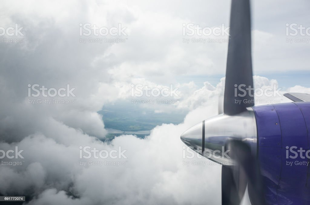 Small Passenger Propeller Airplane in Flight Entering Clouds stock photo