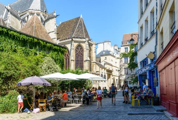Une rue pavée piétonne petite dans le vieux quartier de Le Marais à Paris, derrière l'église Saint-Gervais, avec des gens déjeunant sur la terrasse ombragée d'un restaurant par une journée d'été ensoleillée. - Photo