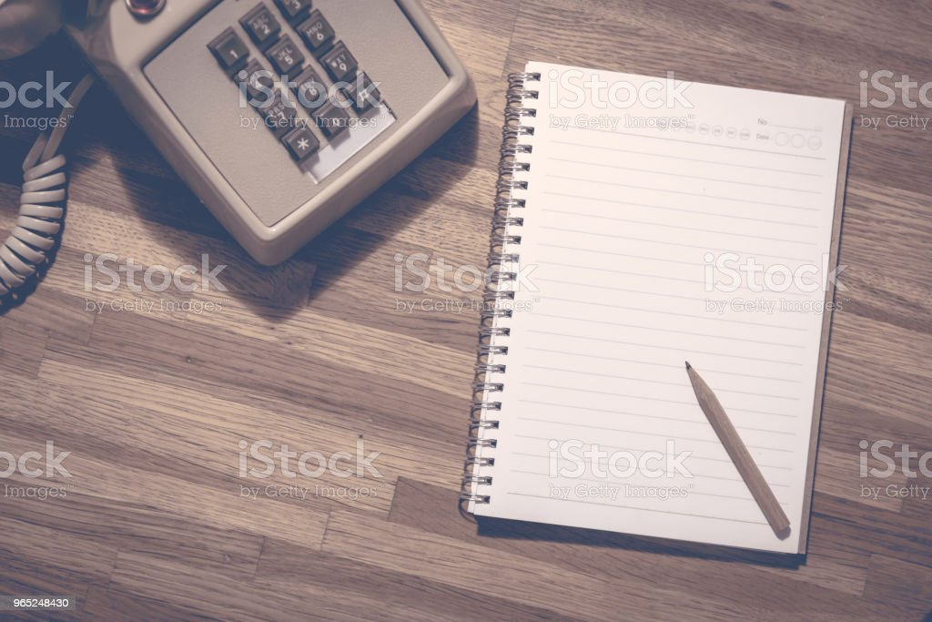 Small pencil on blank notebook with vintage dial phone on wooden table zbiór zdjęć royalty-free