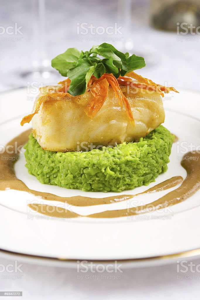 Small piece of sea bass with condiments on a white plate stock photo