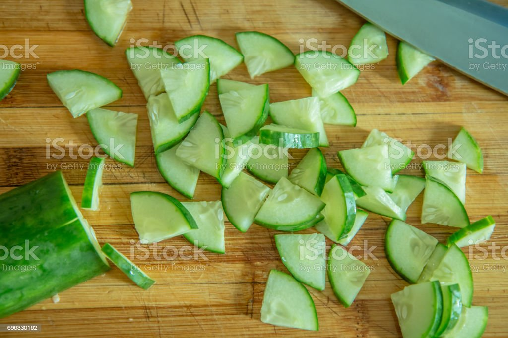 Small pieces of cucumber for salad on a wooden cutting board and cook knife stock photo