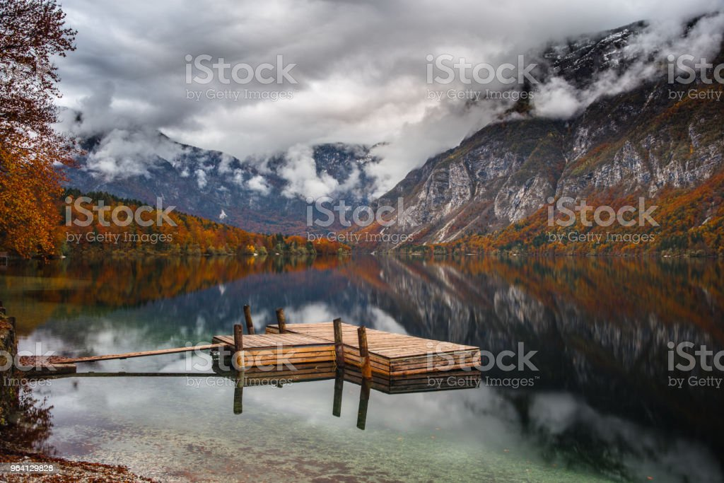 Small pier at lake Bohinj in Slovenia during autumn season. stock photo