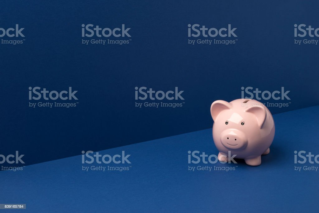 Small Piggy Bank Over Blue Background Copy Space stock photo