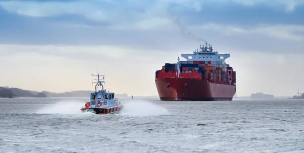 een kleine pilot boot voor een enorme containerschip aan de rivier de elbe, duitsland - industrieel schip stockfoto's en -beelden