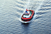 A small pilot boat sails on the sea. Texture of blue water in the sea on the sunset