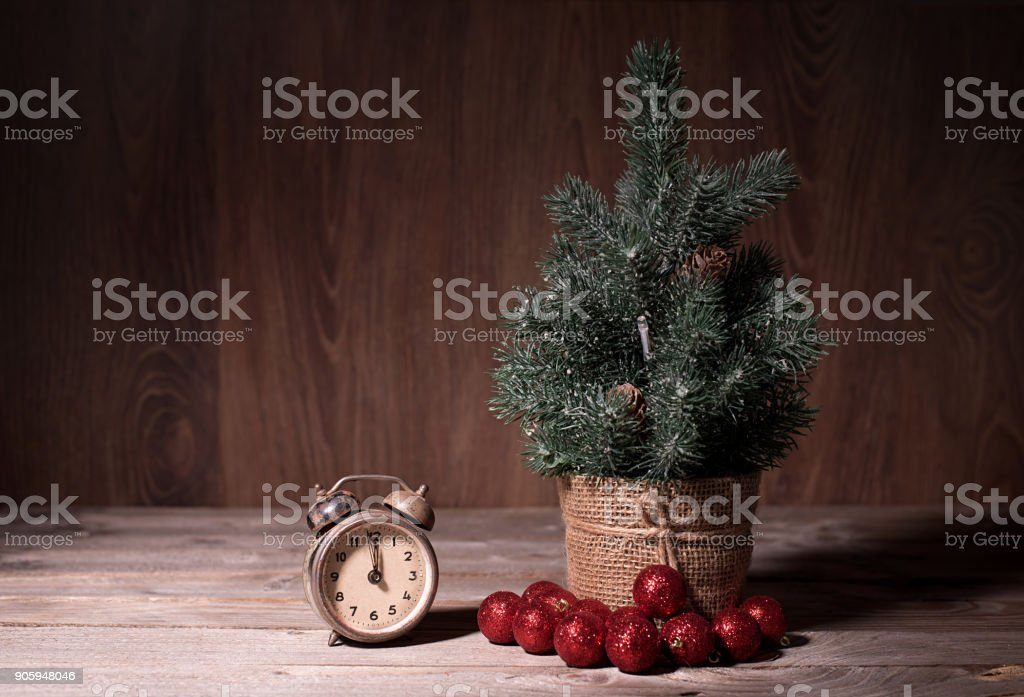Small pine tree and old clock on wooden table stock photo