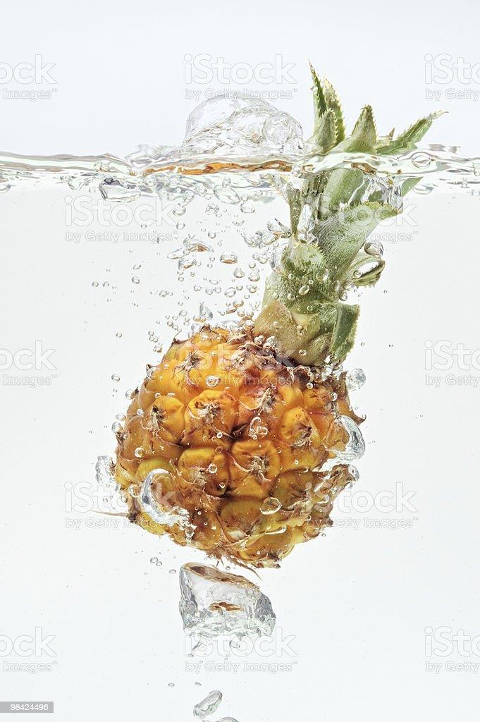 Piccolo ananas cadere in acqua su bianco foto stock royalty-free
